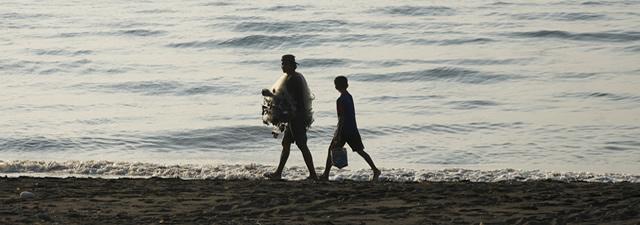 Strandwandeling langs de kust van de Bali zee Indonesië.