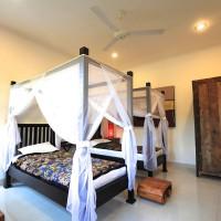 Slaapkamer met twee ruime éénpersoonsbedden voorzien van klamboe.