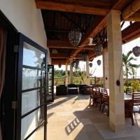 Het overdekte terras van de vakantievilla op Bali met uitzicht op de zee.