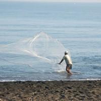Man vist met net op strand van Bali.