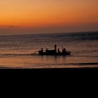 Een vissersbootje op de Bali zee bij het ondergaan van de zon.